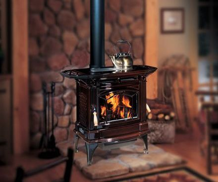Regency H300 Hampton Cast Iron Wood Stove Fireplace brown with a tea kettle on top