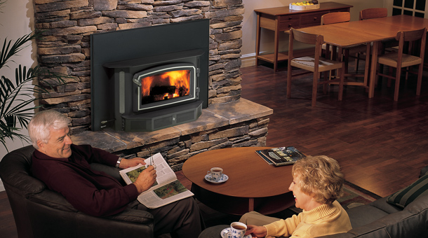 Couple comfortably sitting near a Regency Fireplace i3100 Wood Insert with Stone Surround and mantel