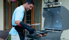 man happily grilling on a weber barbecue